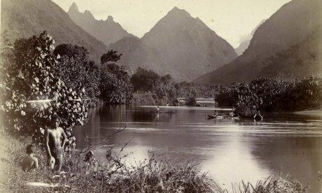 Early photograph of native fishermen in a river with mountains in the distance