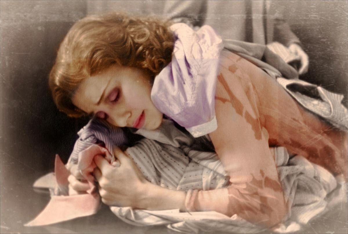 film still of a woman covered in shirts and weeping