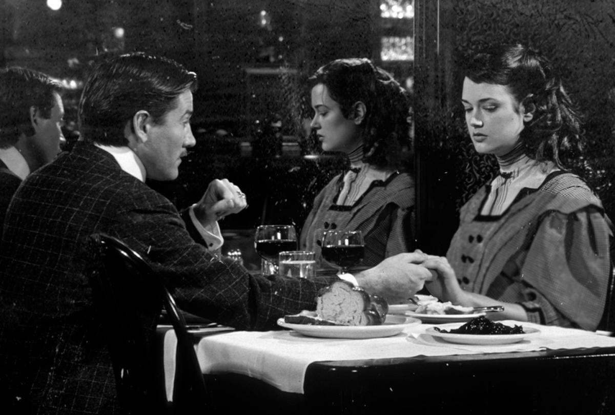 black and white film still of a man and woman holding hands across a table