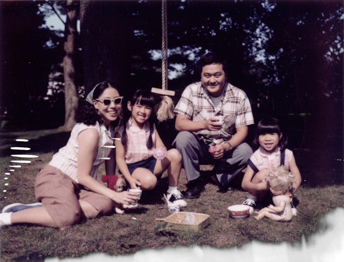 family sitting on the grass, smiling