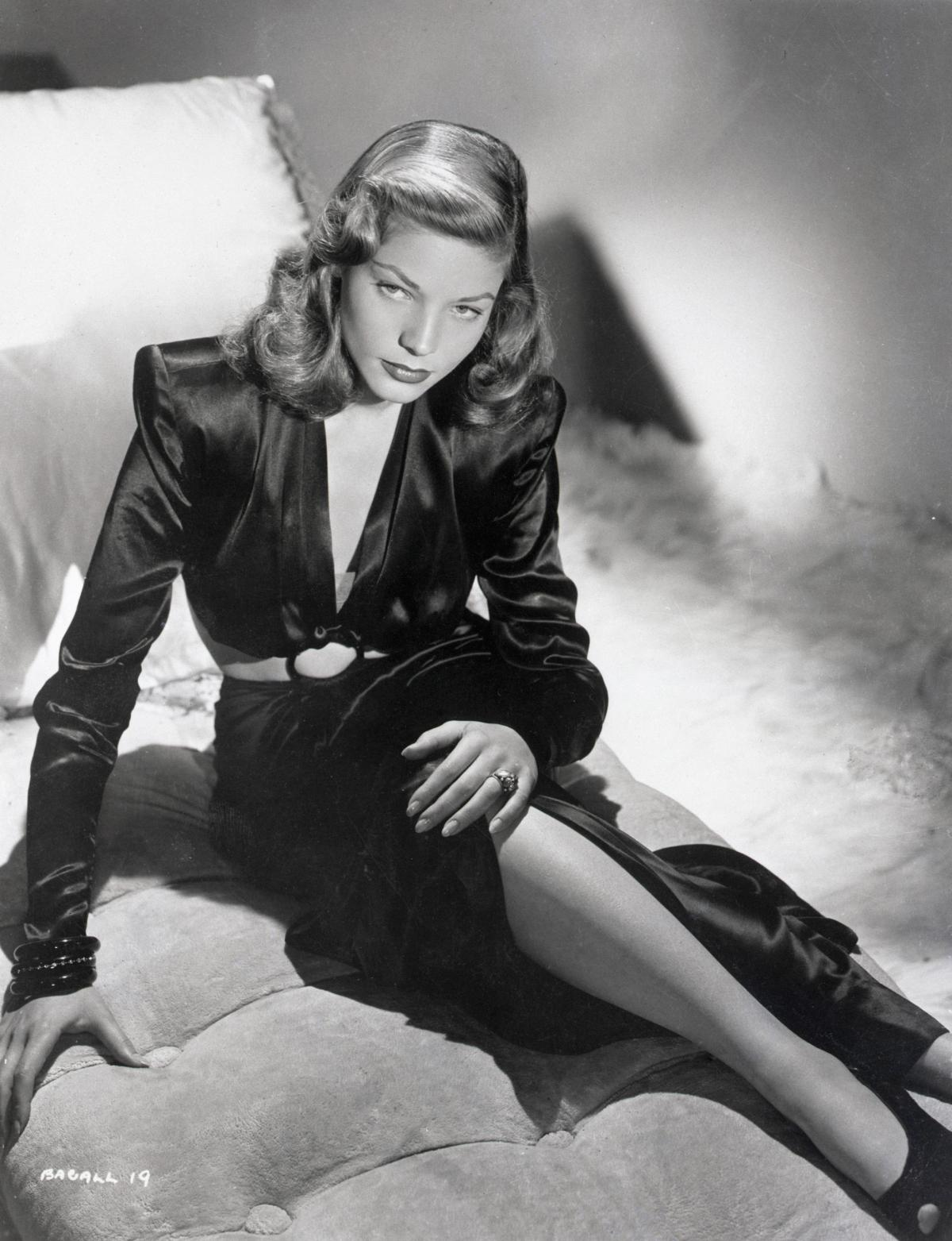 Bacall sits with her legs crossed on a cushion, wearing a long black dress with a v neckline, heels, and with her hair in curls