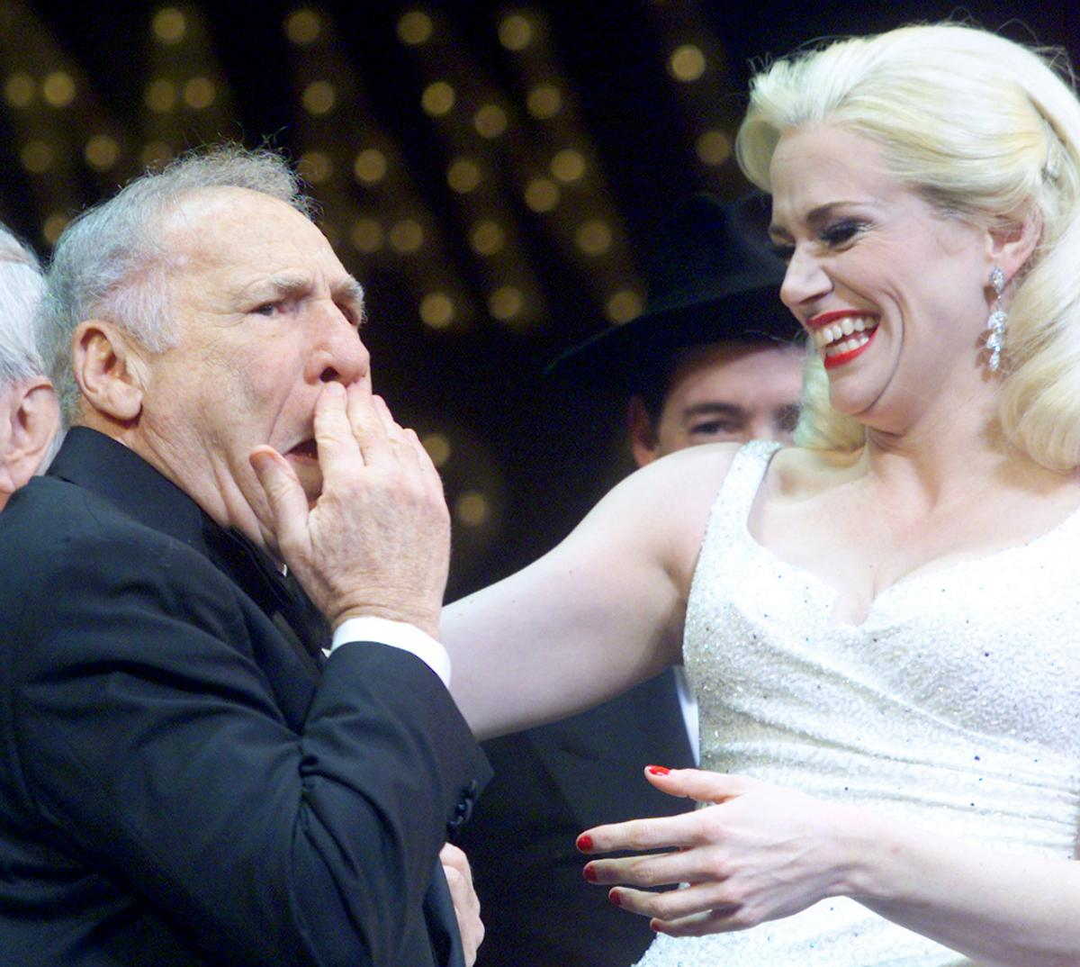 Brooks holds his hand to his face in surprise as a blonde actress in a white dress reaches out to embrace him