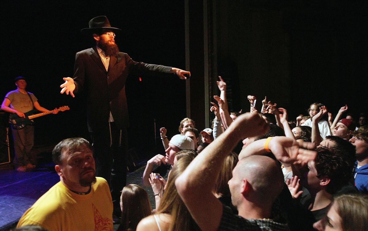 Matisyahu on stage, in a black suit and black hat, points to a crowd of concert goers while performing