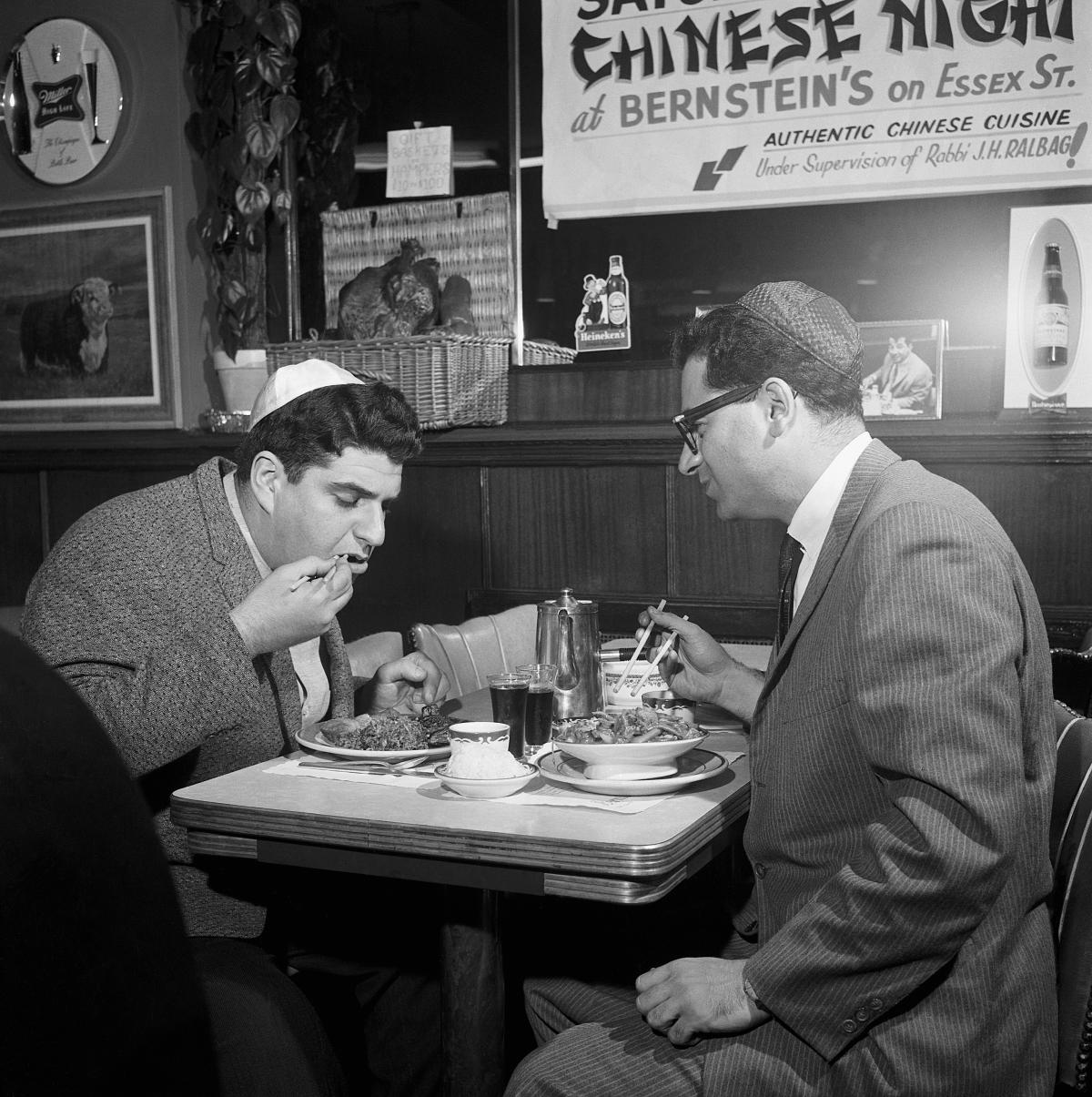 Two men wearing yarmulkes sit at a diner table, eating chinese food with chopsticks