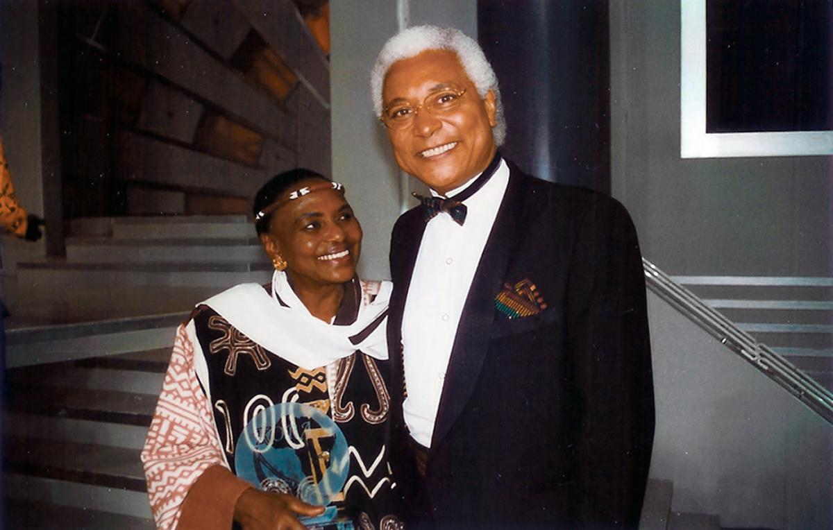 Collinet in a black tuxedo smiles at the camera, next to Makeba, wearing a thing beaded band around her forehead, and smiles at him