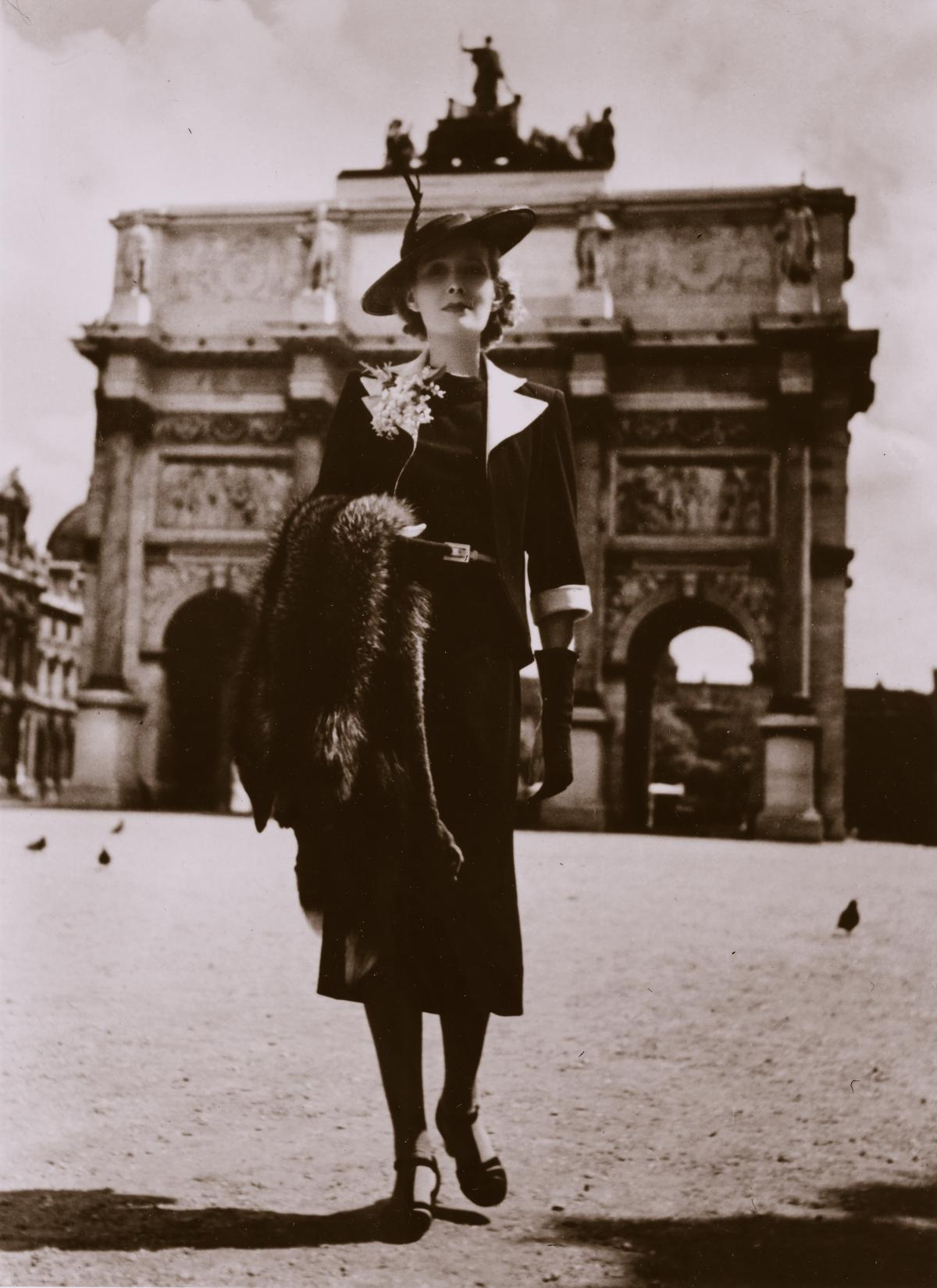 Bedwell, wearing black dress, pumps, black jacket with white collar, and a flat black hat with a feather, carrying a fur stole, in front of the stone Arc