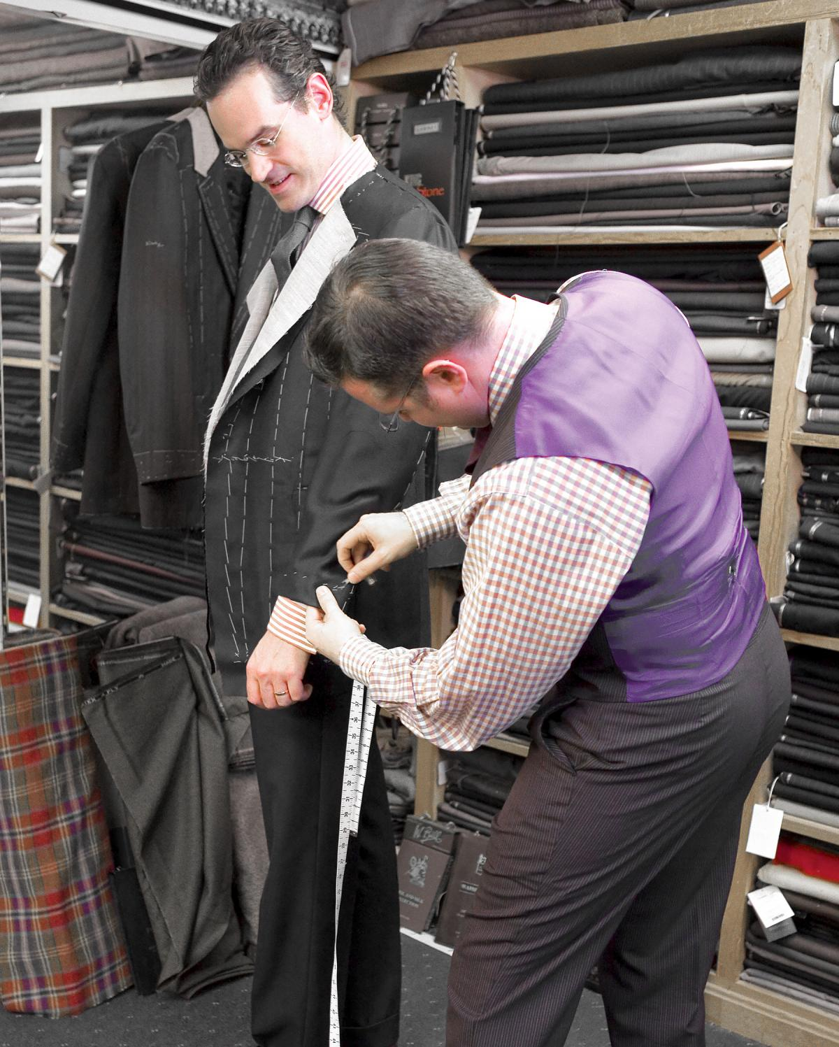 A tailor in a purple vest measures the cuff on Anton's suit jacket