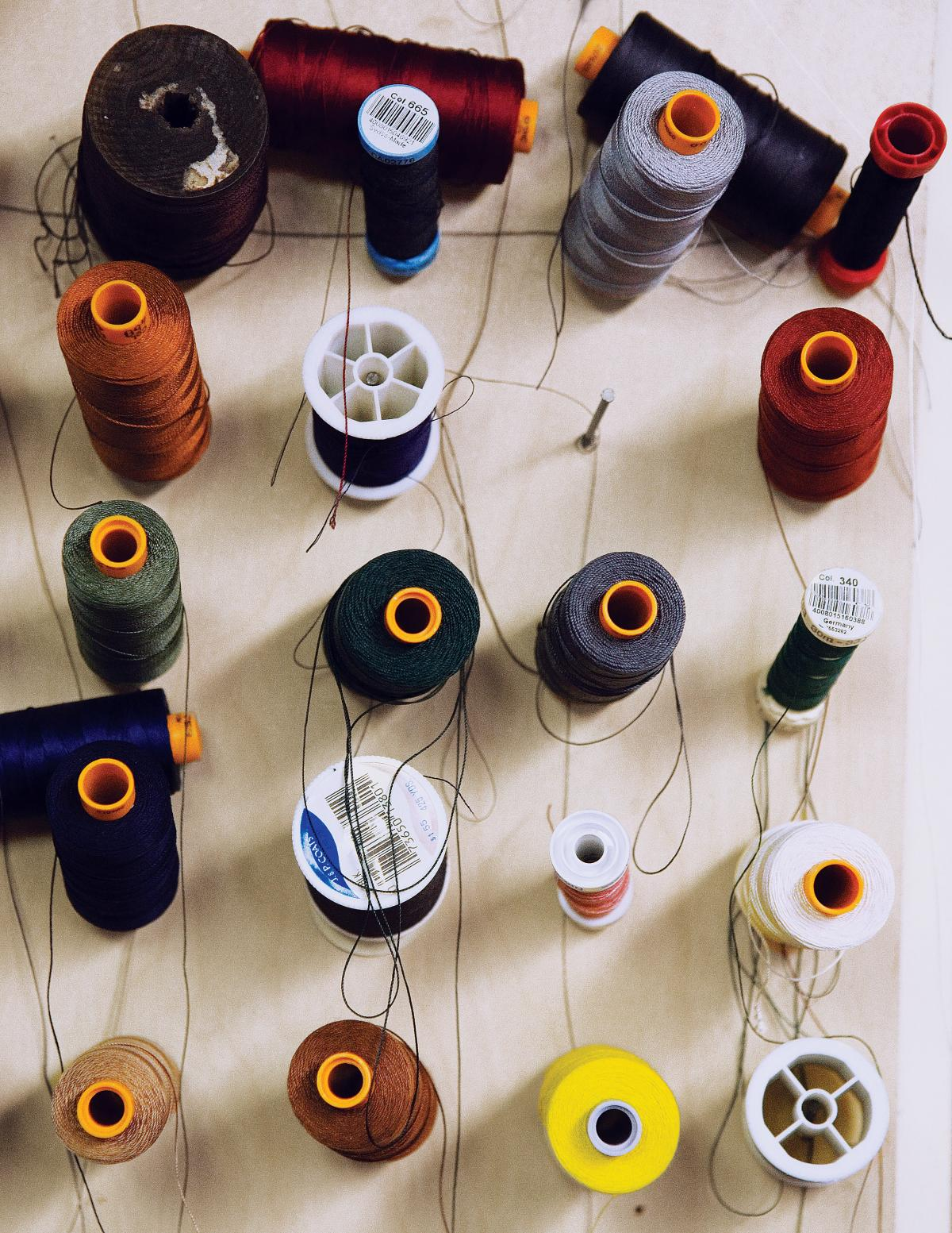 Multiple spools of multi-colored thread are arranged on a white wood table
