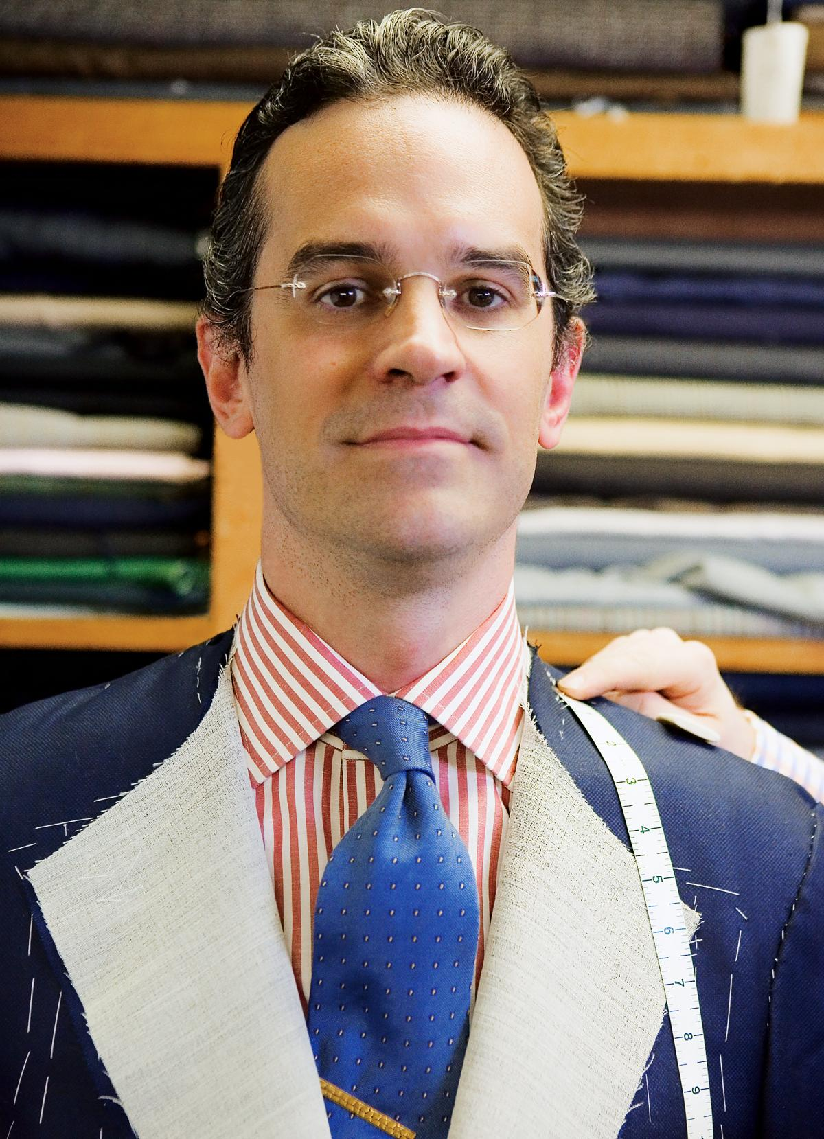 Anton looks directly at the camera while getting measured for a new, navy blue suit, which he wears over a red and white striped shirt and cobalt blue tie