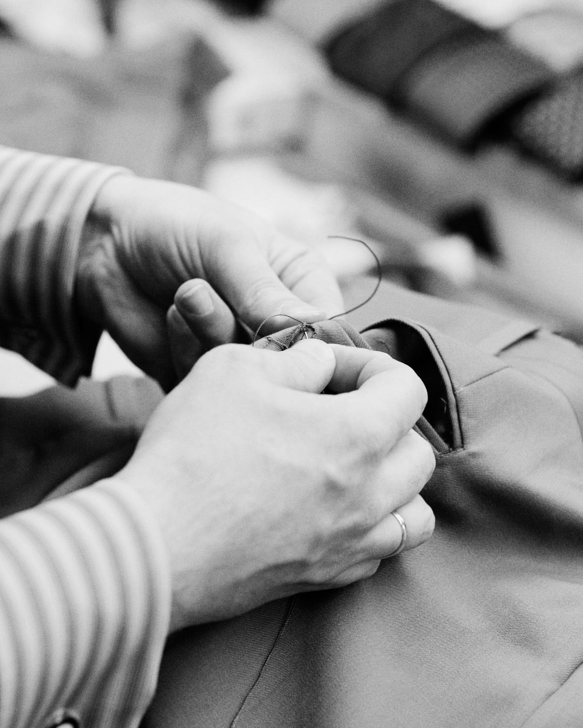 black and white photo of a pair of hands hand sewing stitches into a suit