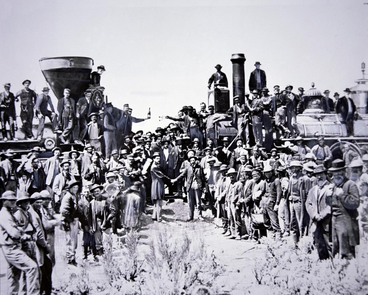 Black and white photograph of railroad workers standing on top of and in front of trains