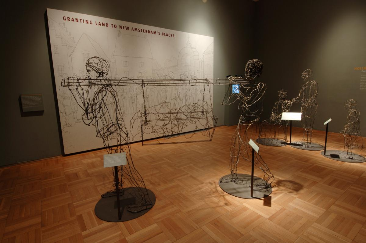 2 men sculpted out of wire, holding a beam between them