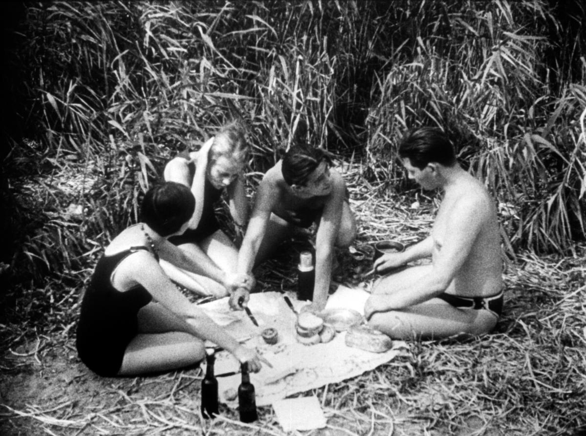 black and white photo of three women and a man sitting on the ground