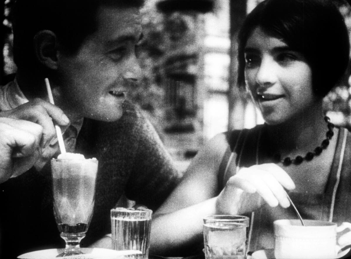 black and white film still of a man and a woman drinking out of glasses at a table
