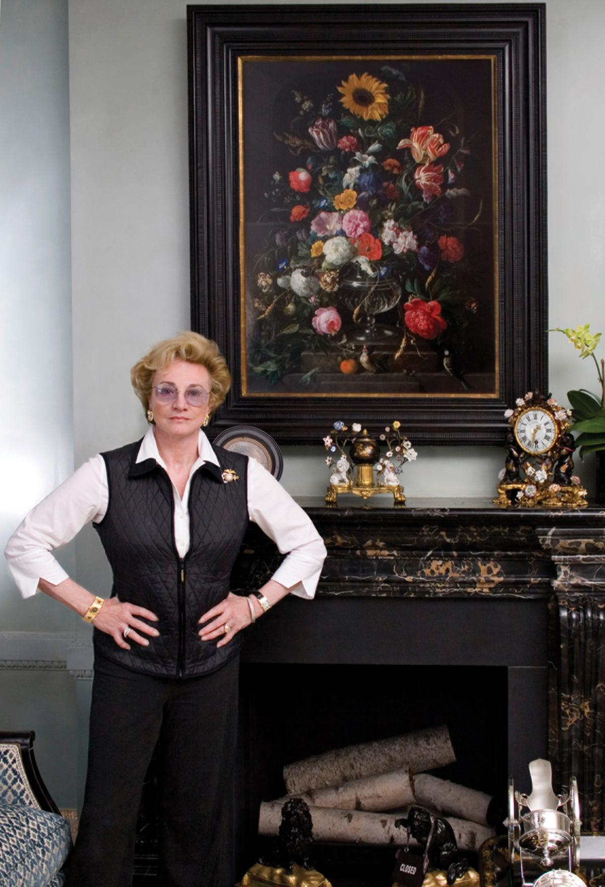 Photograph of a woman standing in front of a painting that hangs above a fireplace