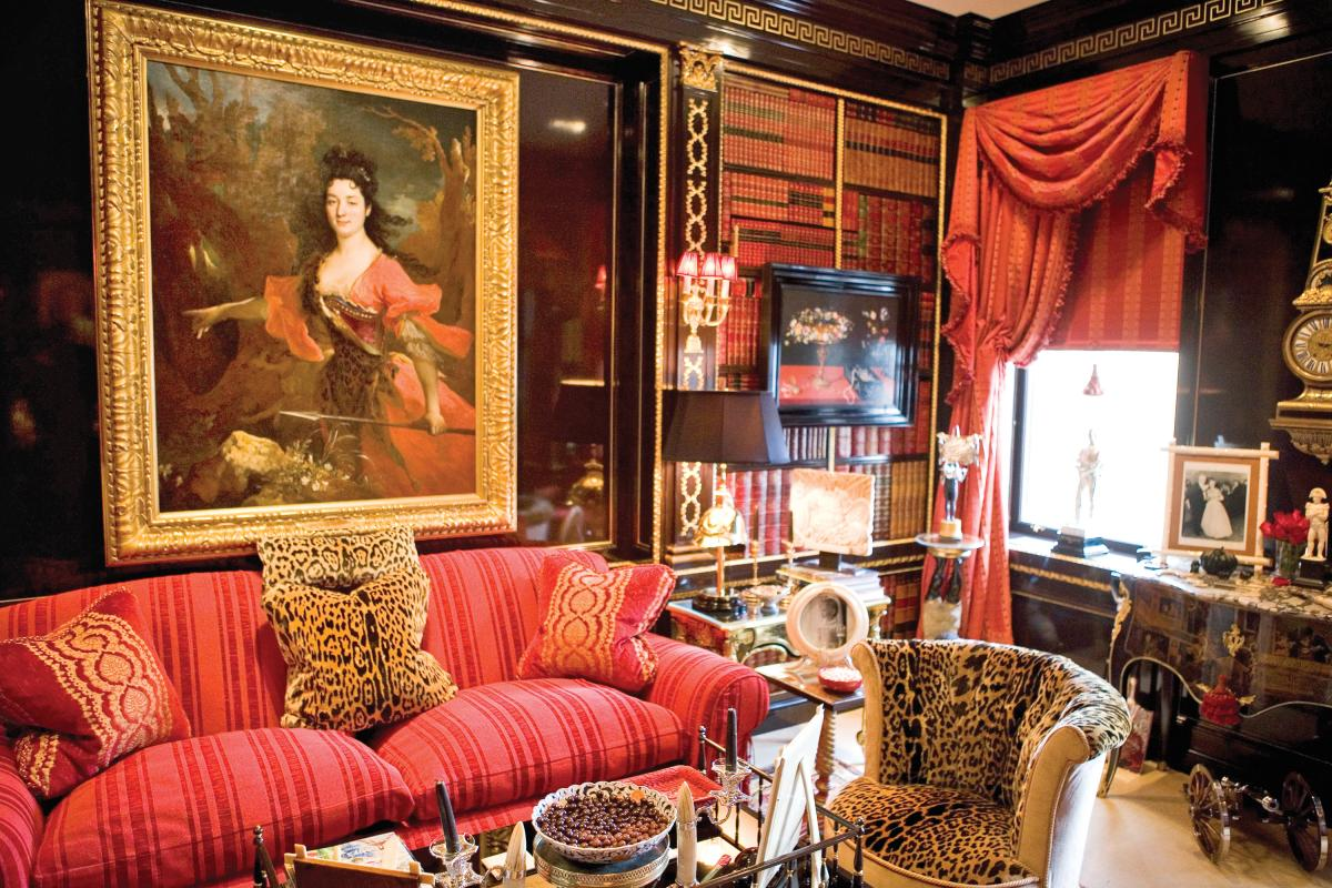 Photograph of a sitting room with a red couch, large oil painting, dark walls