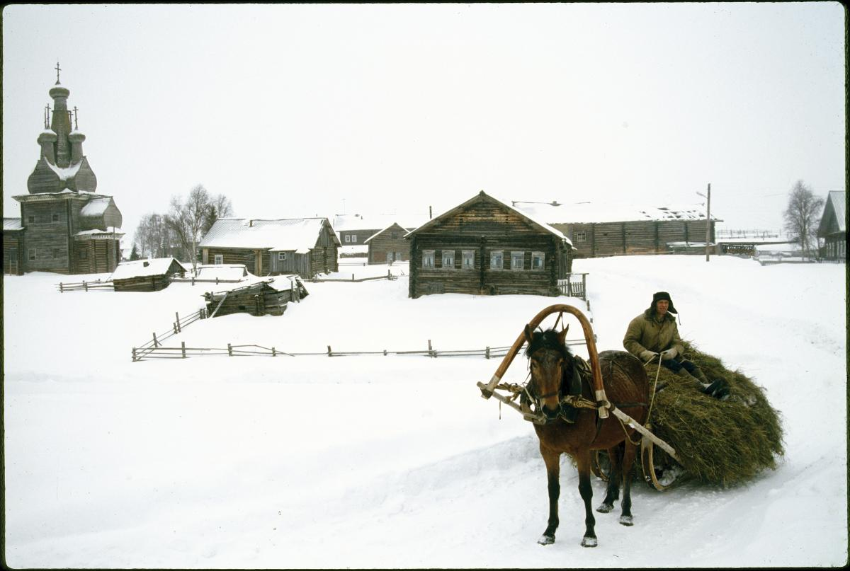 Photograph of a snowy landscape, man in cart being pulled by horse, log house in background