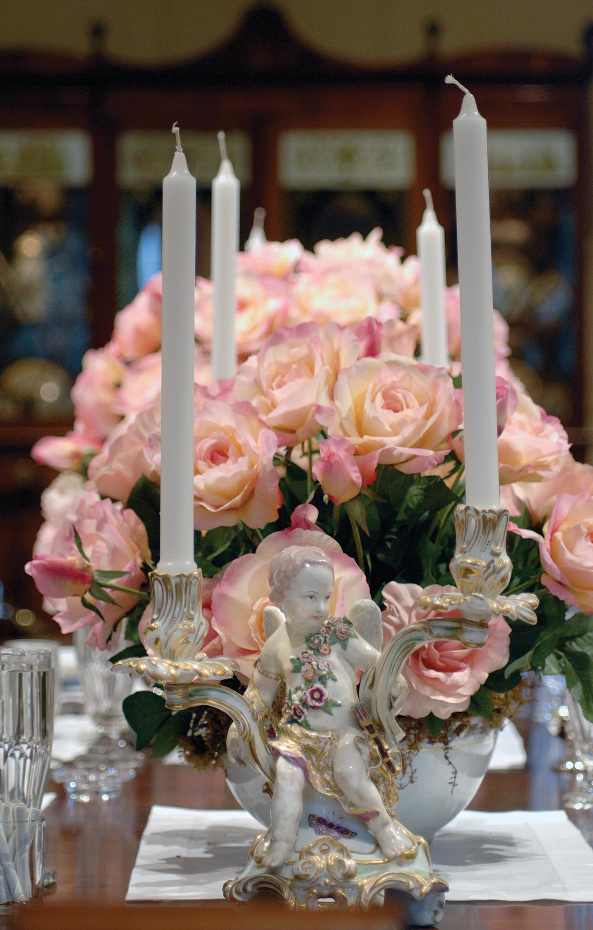 Photograph of candelabras, pink roses in a bouquet