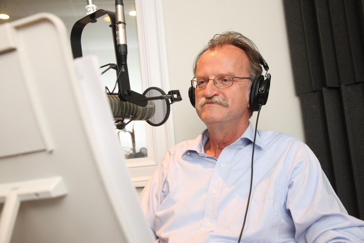 Onuf wearing headphones, standing at a recording microphone