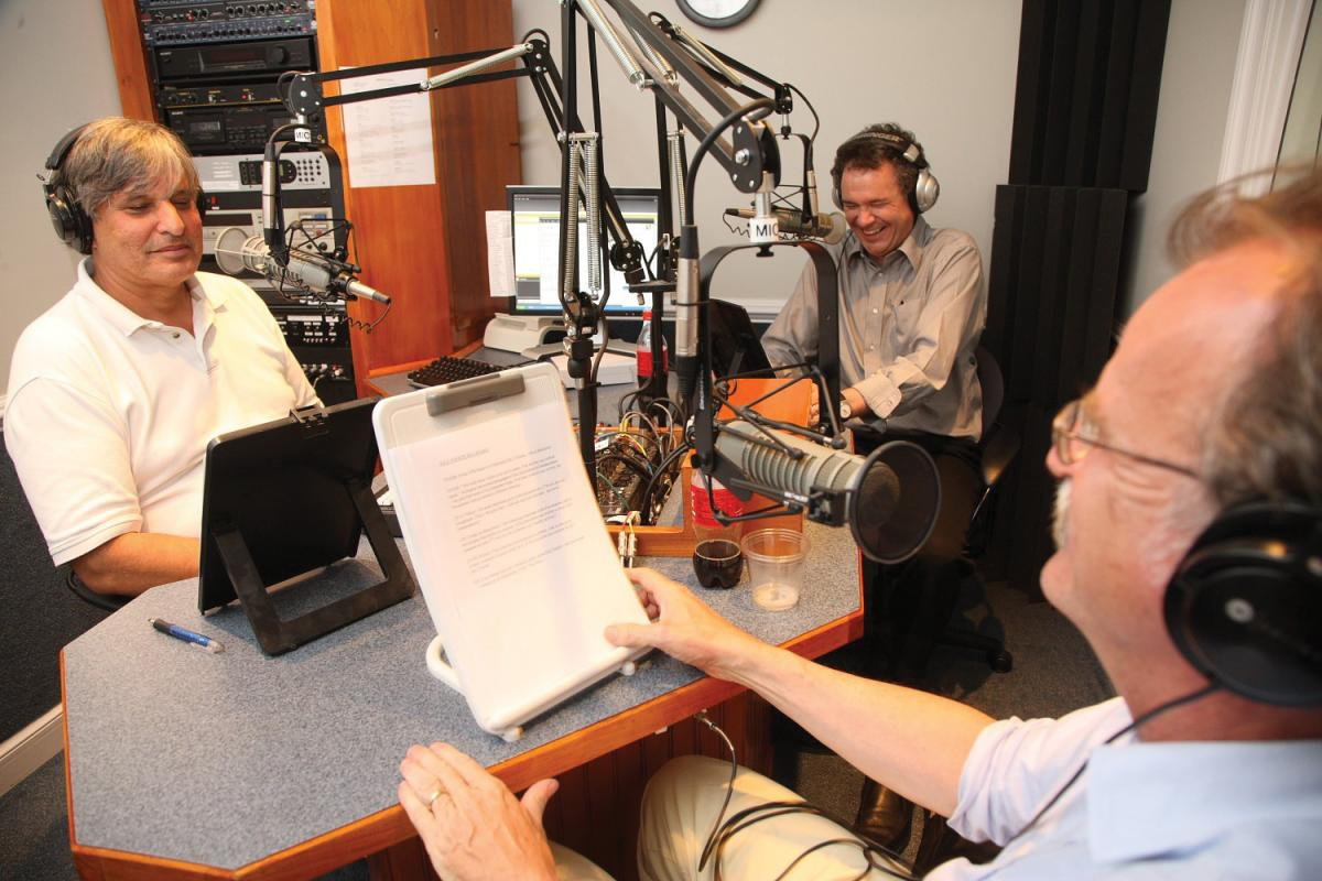 The three hosts look at clipboards of notes while recording a session, wearing headsets and sitting in front of their mics