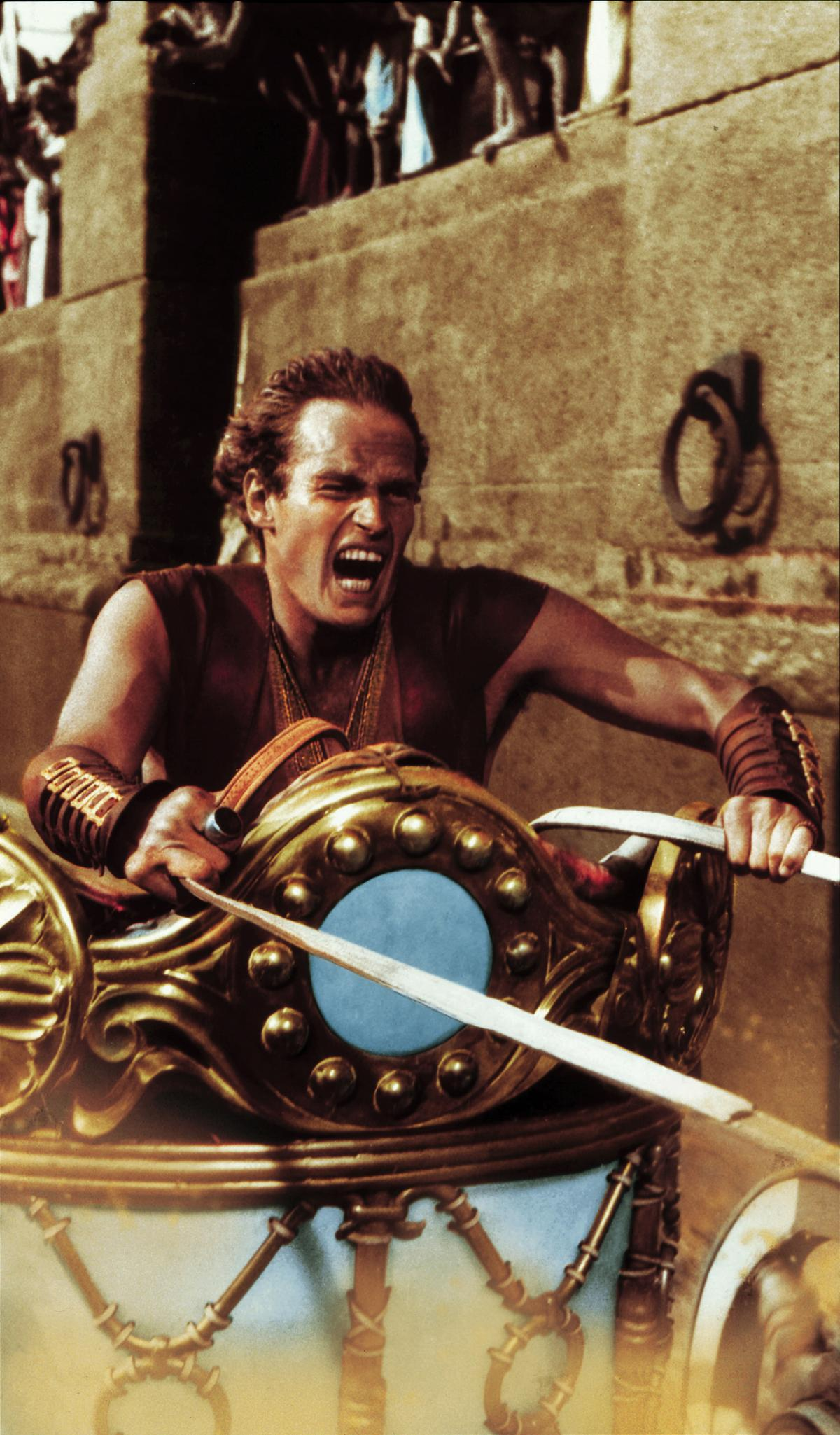 Heston, yelling, pulls on the reins of a chariot during a scene in Ben-Hur the movie
