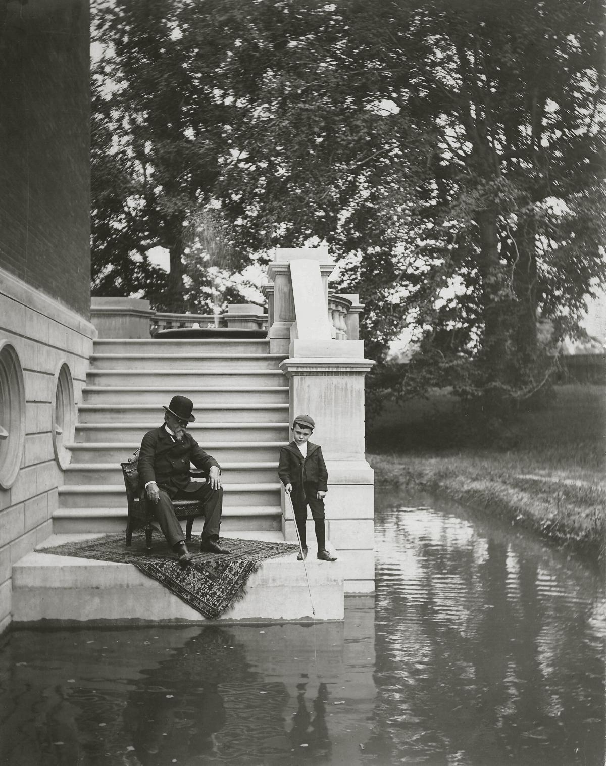 Wallace, in a bowler hat and dark suit, sits on a chair and looks down into the moat, while his grandson dips a short pole into the water
