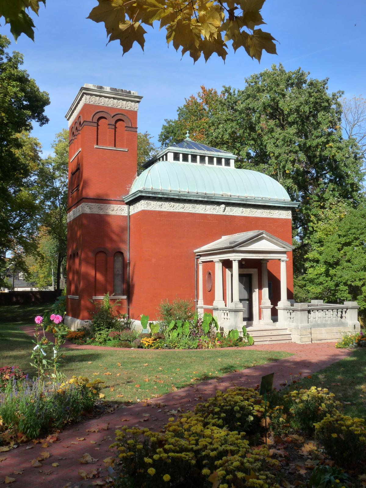 Red brick building with a teal roof and white porch columns, surrounded by green gardens and trees
