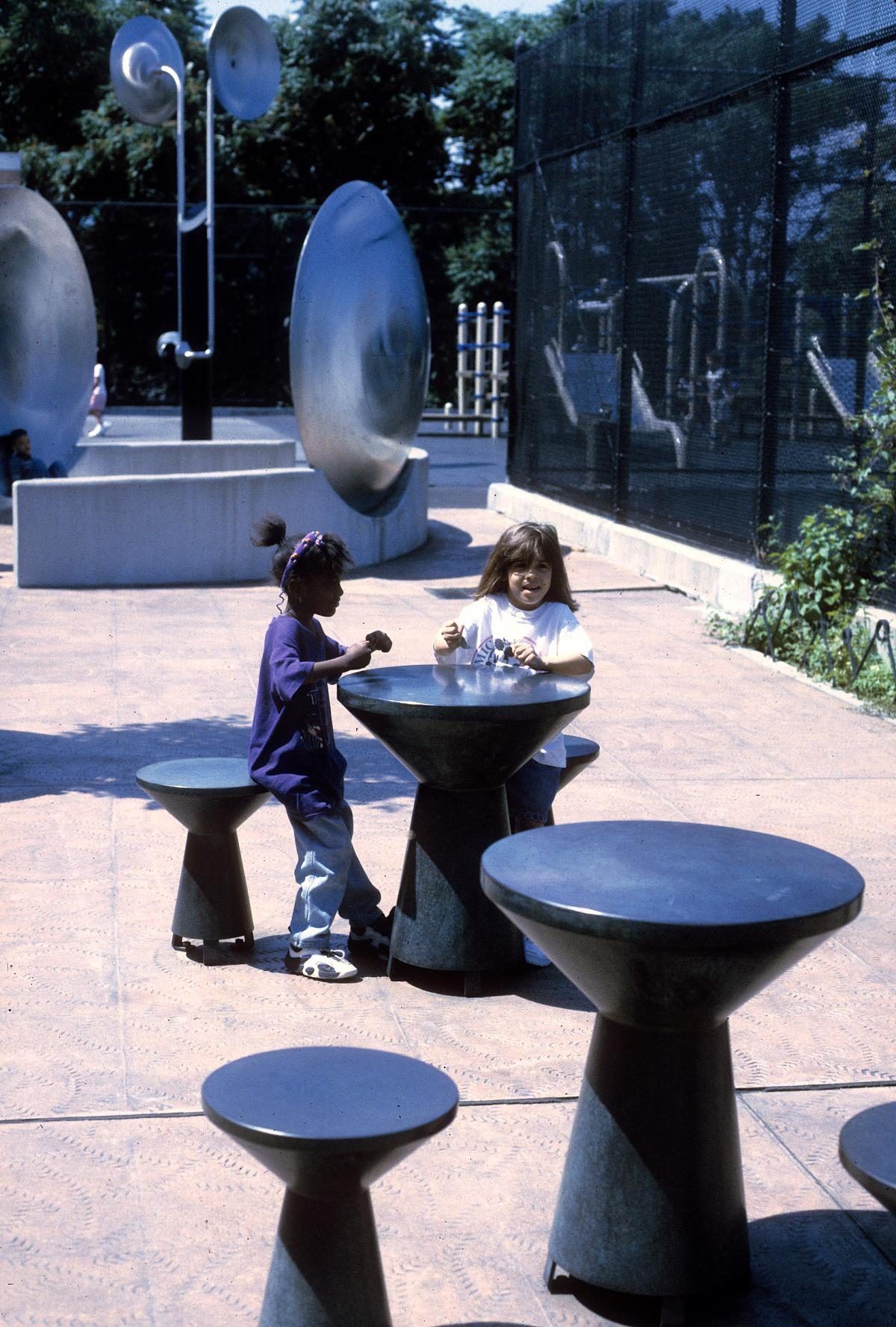 Two girls play at a mushroom-shaped table