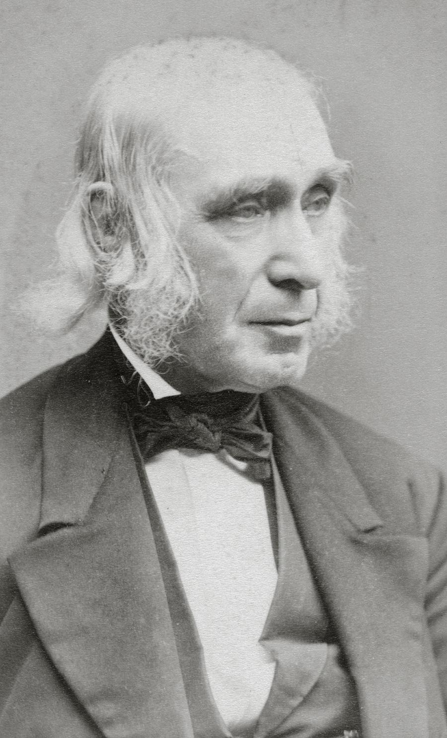 Alcott in a black suit and bow tie, facing slightly to his left