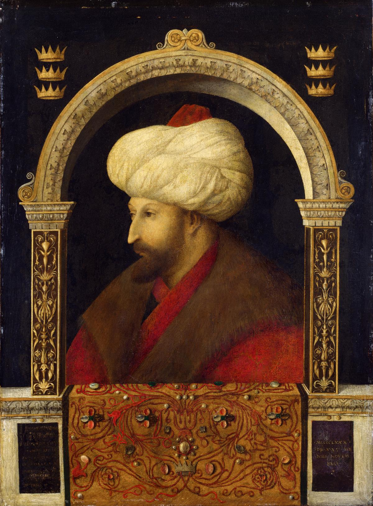 A man wearing a white turban, brown fur collar and red robe, framed by a golden arch