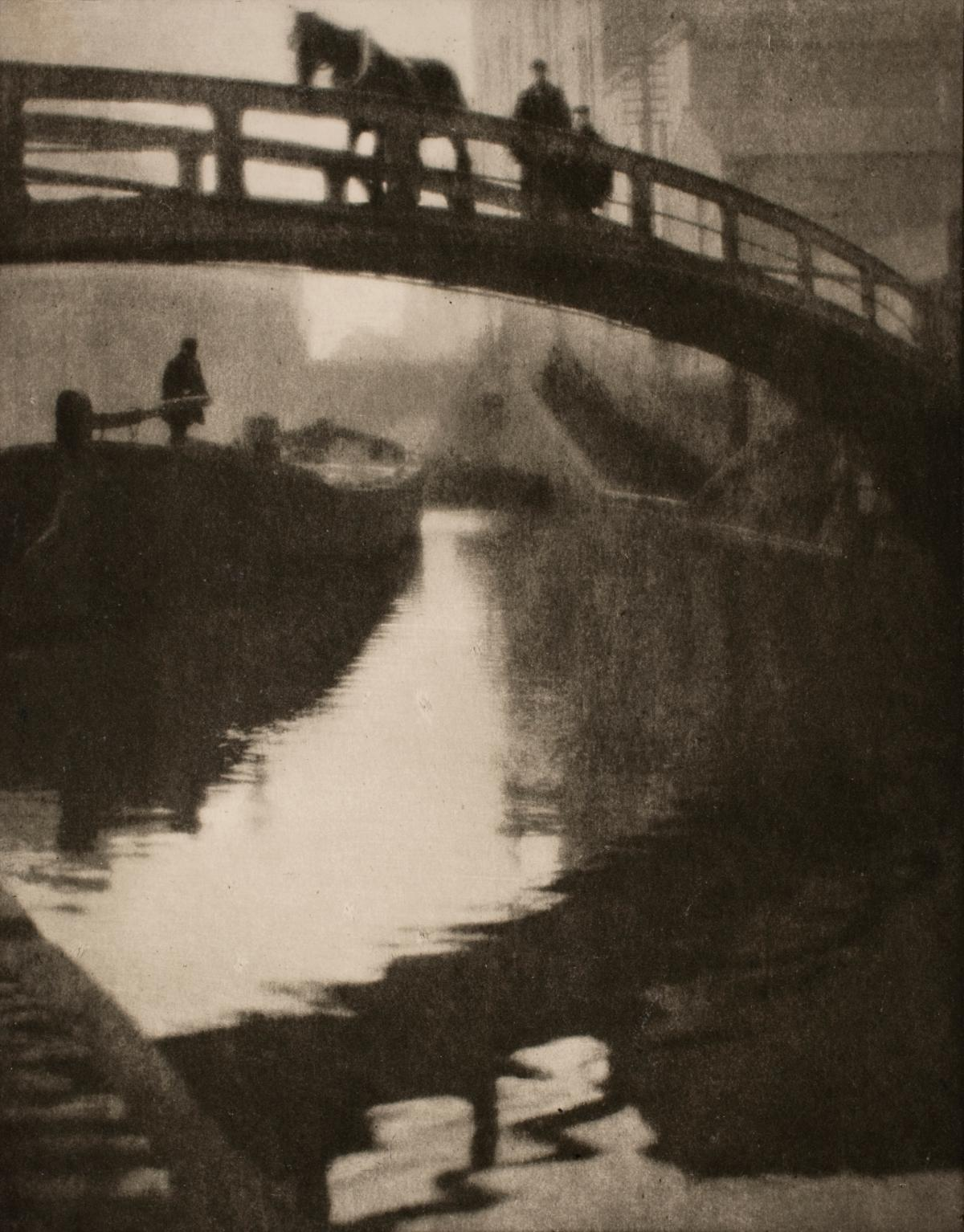 From the point of view of someone on the canal water: a bridge with a man and his horse crossing, with a boat up ahead, manned by a single figure, all in shades of black and beige