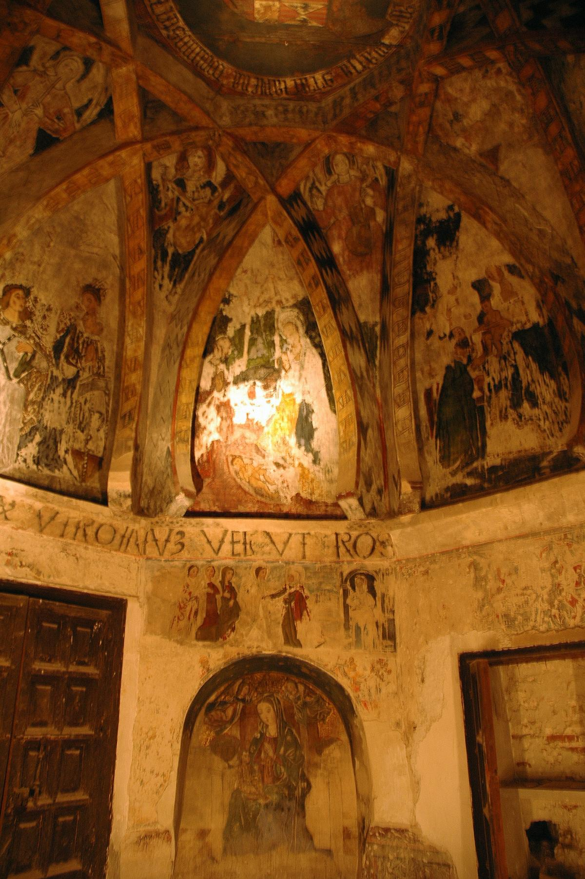Paintings of saints adorn the vaulted ceiling, lit by torchlight