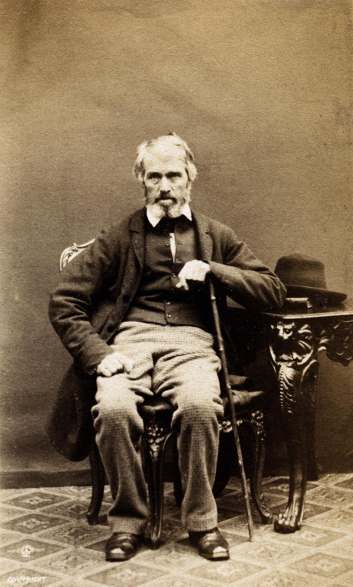 Carlyle sits, resting his left forearm on a walking stick, dressed in grey trousers and a dark coat, his hat sitting on a side table on his left