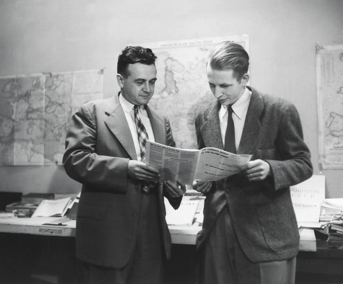 The two men look over a newspaper together, in an office hung with maps