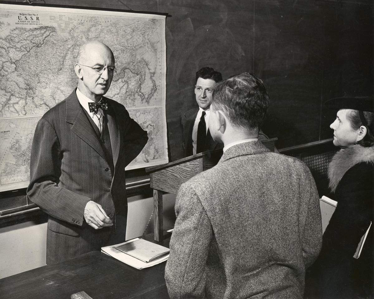 Robinson speaks to two students, his back to a large map and blackboard, while Mosely stands off to his back left