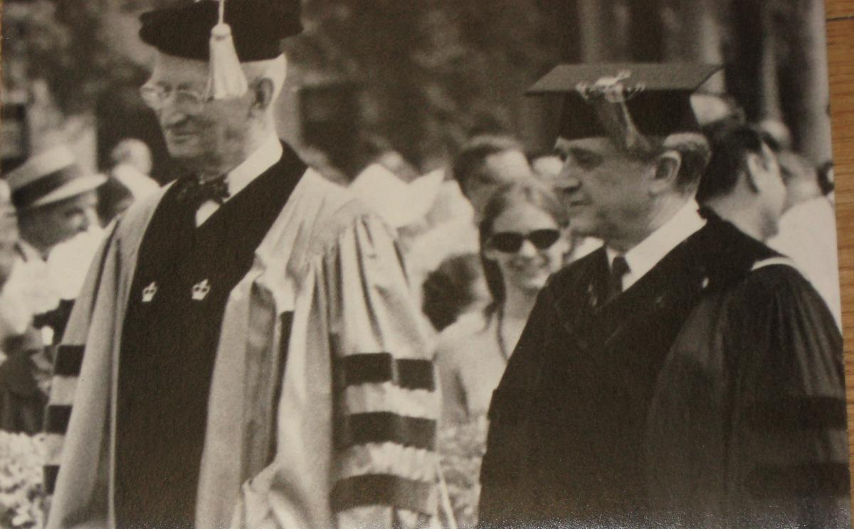 Mosely in dark collegiate robes and mortarboard cap, walks next to Robinson, who is in Columbia's blue and black robes and tasseled cap
