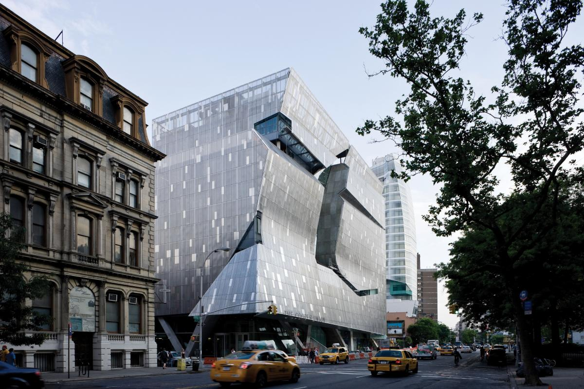 the new building is created out of silver rectangular panels, with parts of the wall curved inward