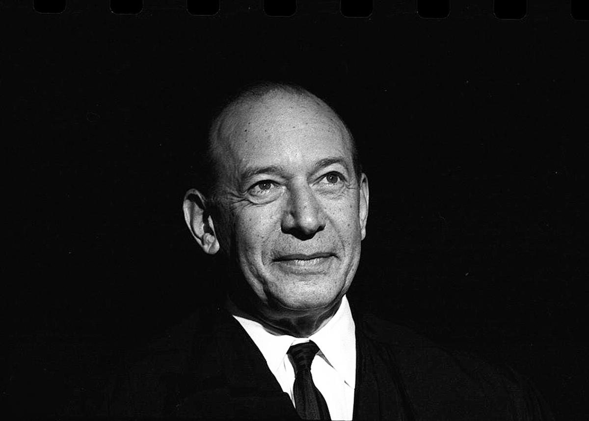 Black and white photo of Fortas, looking off into the distance, smiling slightly, wearing a dark suit and tie