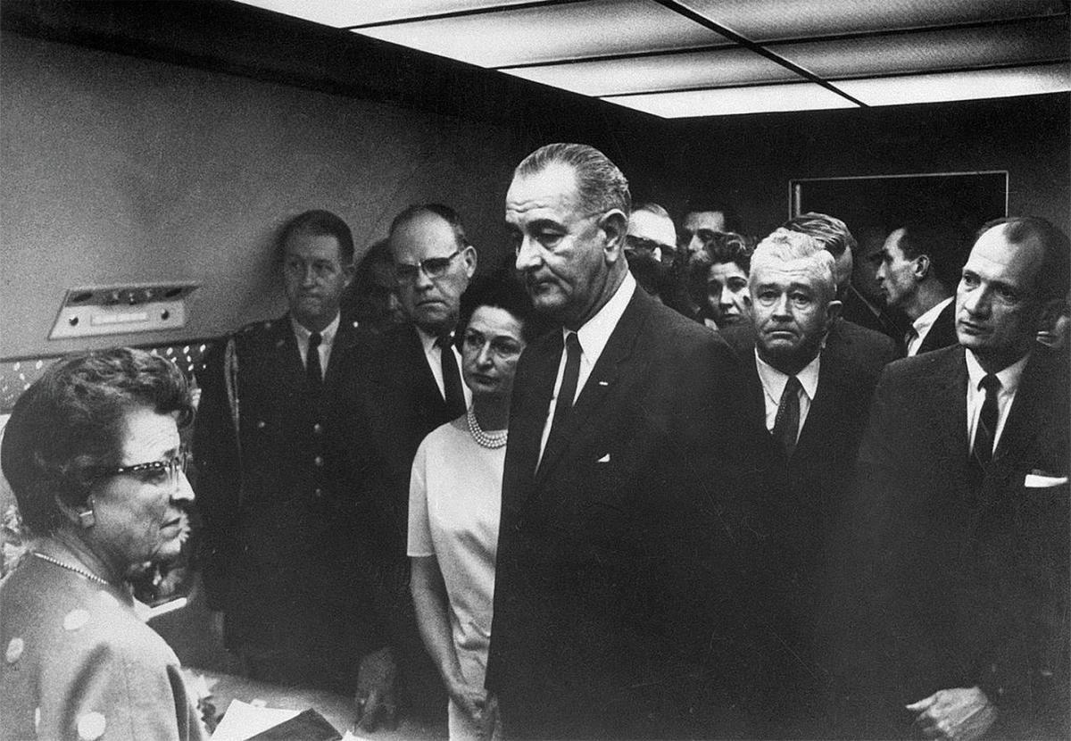 LBJ waits, with a crowd of advisors, including Thornberry, standing behind him