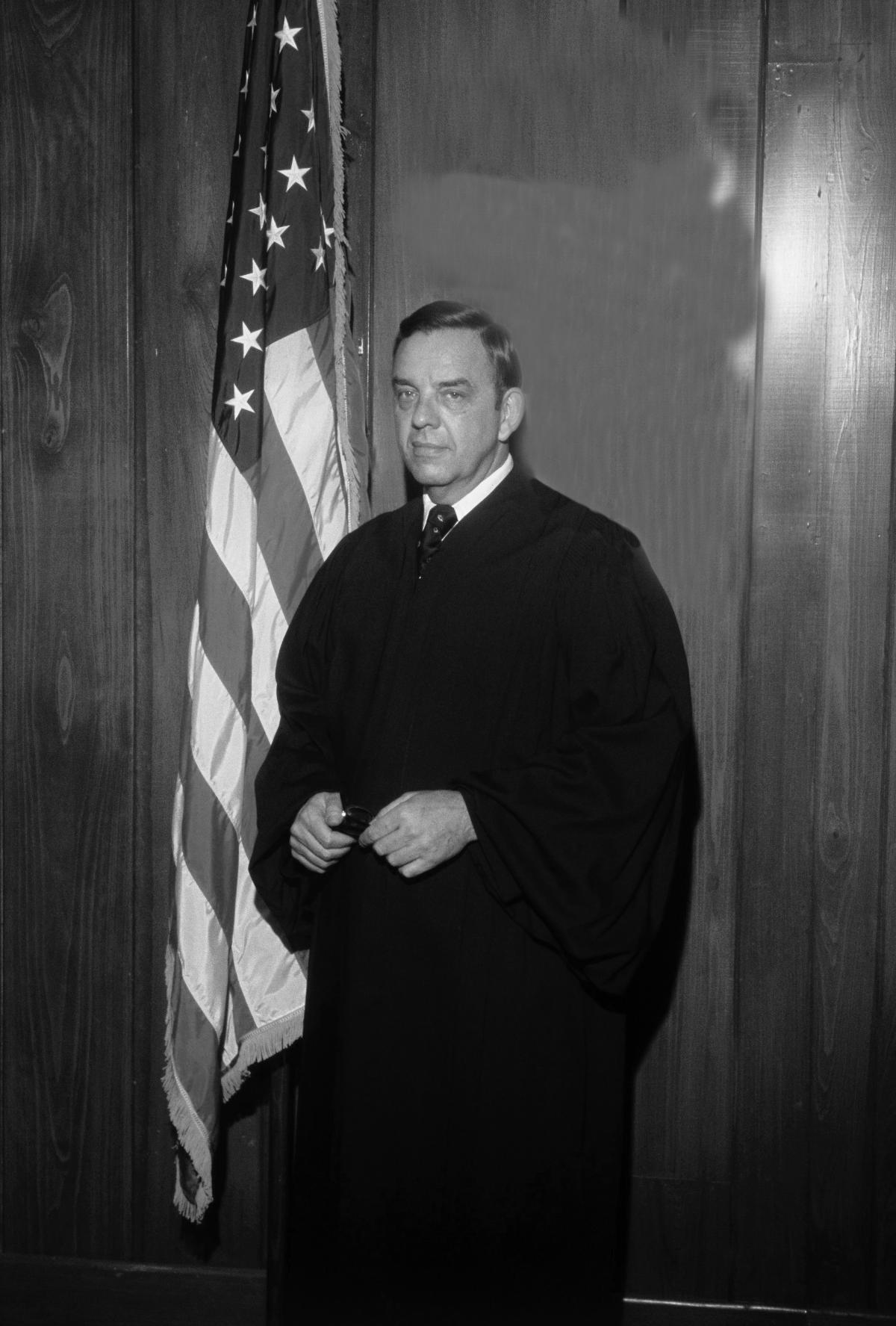Carswell wearing judge's robes, standing in front of the American flag