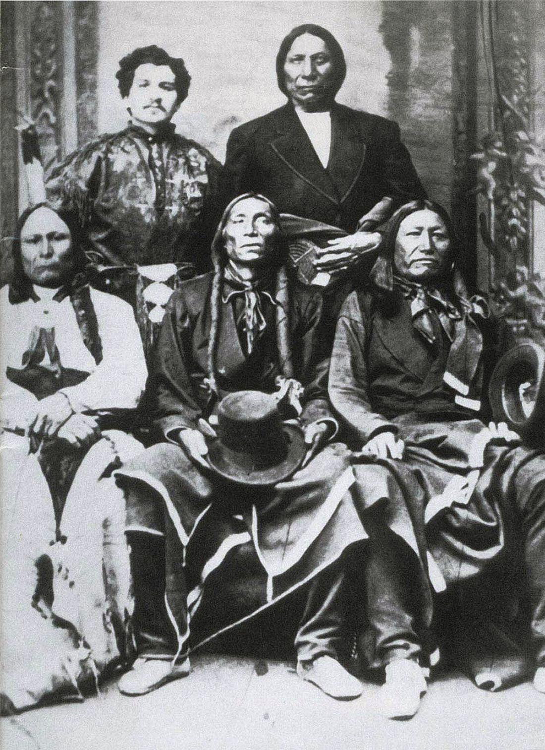 Three seated Pawnee chiefs in traditional clothing, with Mayer and another chief in a western style suit standing behind them,