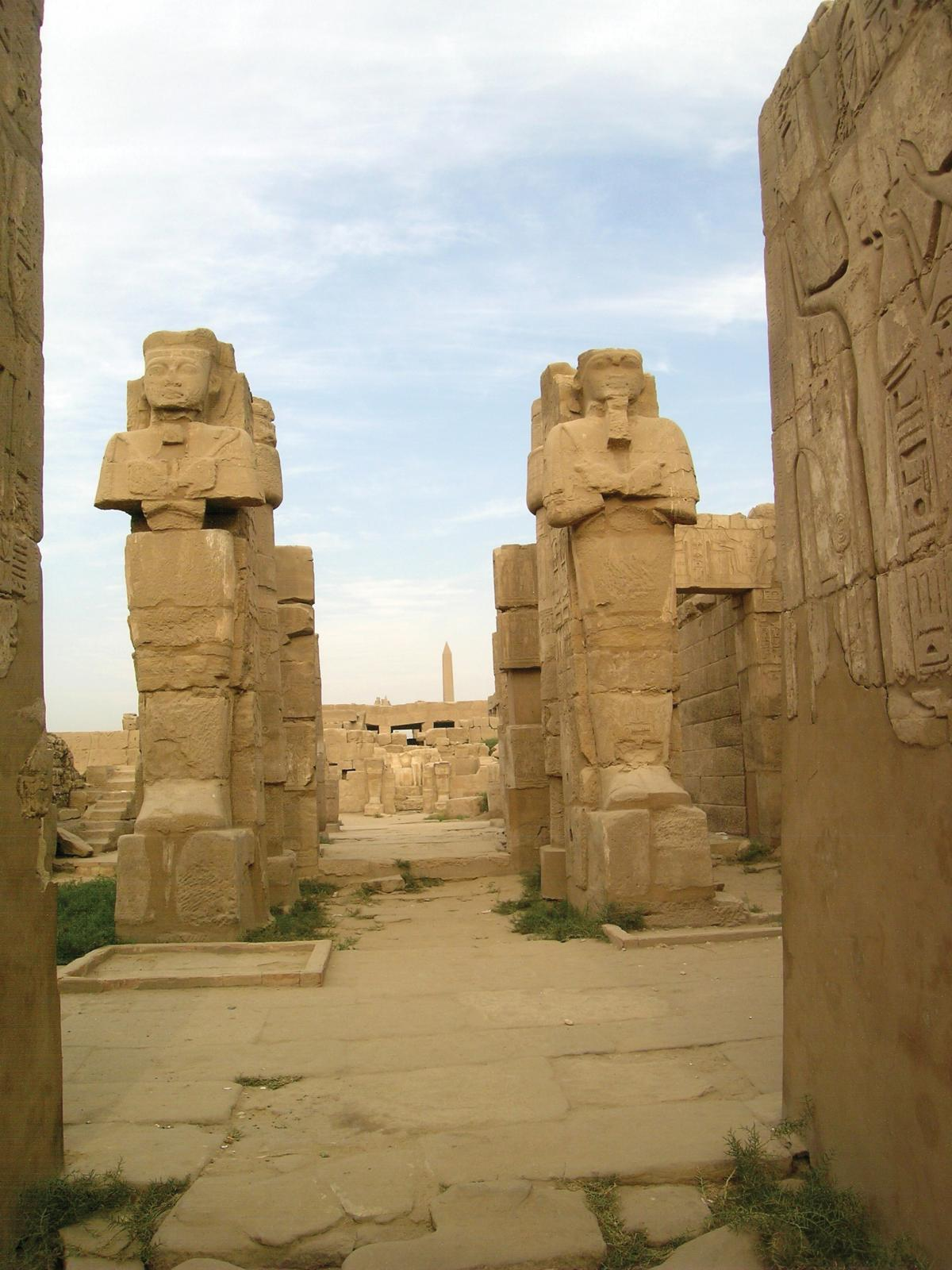 Huge sandstone statues of rulers and gods flank the entrance to a temple, also made of yellow sandstone