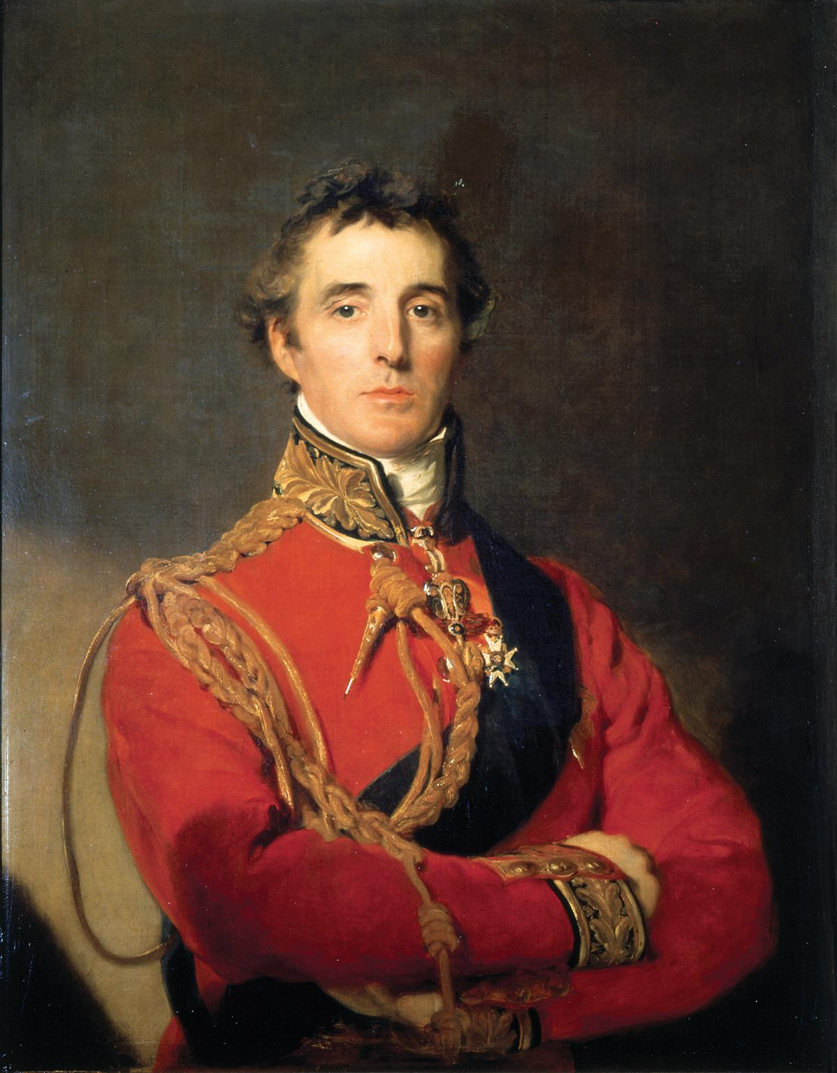 The General in a red tunic decorated with gold braid, with arms crossed across his chest