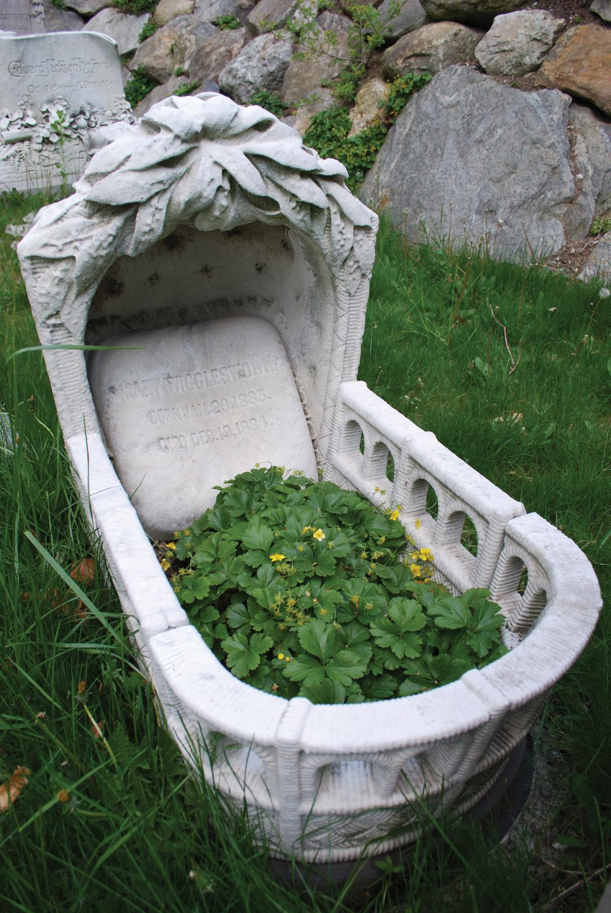 Photograph of a headstone carved into the shape of a cradle