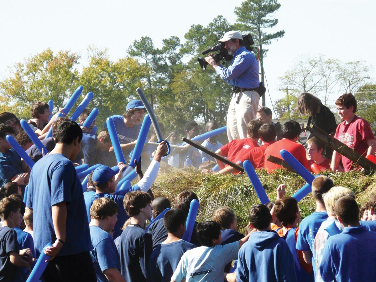 students in blue hold blue inflatable bats while reenacting the battle