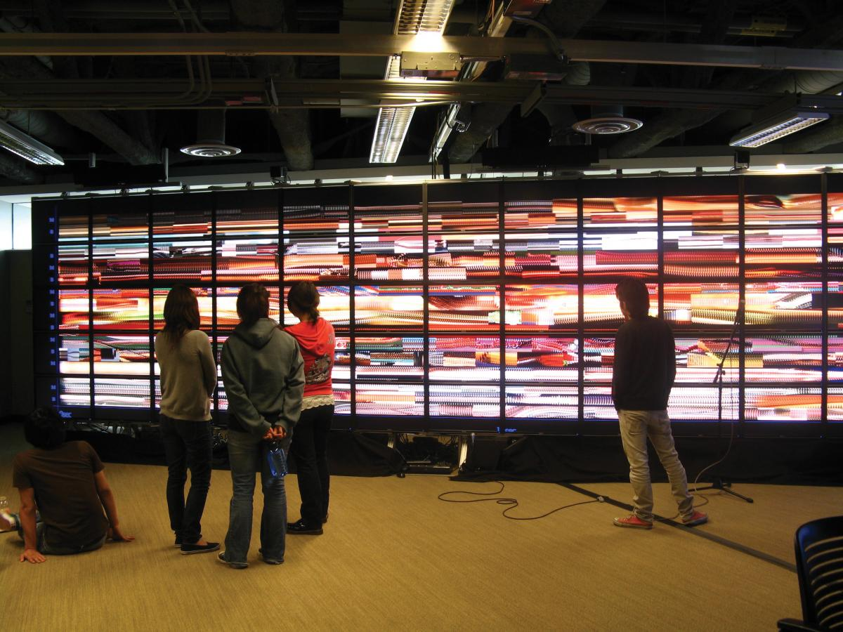 Several people stand in front of numerous small screens set up on a wall