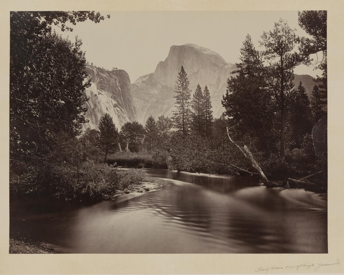 Half Dome, another large rock formation, in the distance, as the backdrop of a calm river and trees