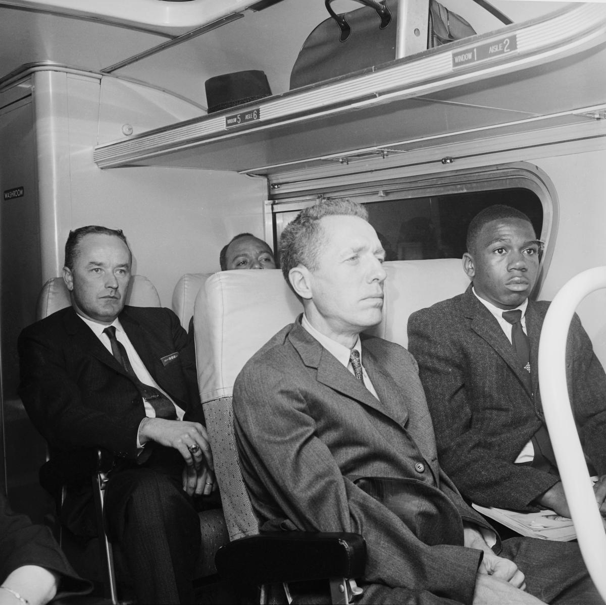 A white man and an African American man, in suits, sit next to each other on one of the Freedom Riders' buses