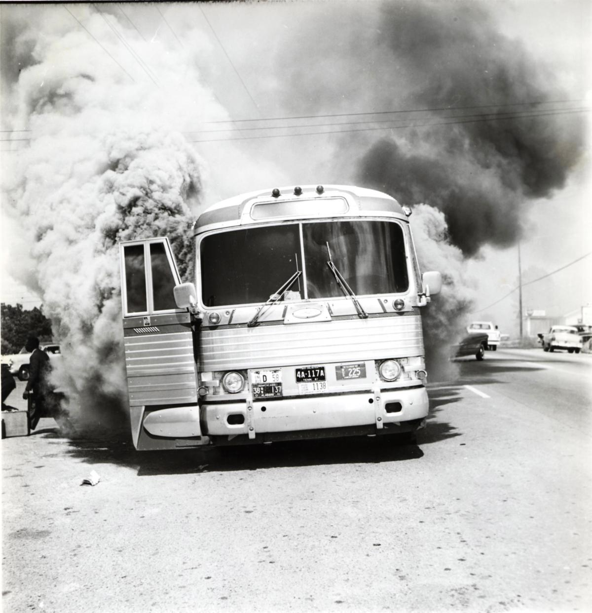 Smoke billows out of a Greyhound Bus with its doors wide open