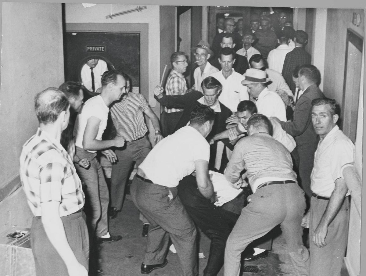 A fight between whites and African Americans; several bystanders watch